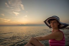 Stylish young woman in a straw sunhat relaxing on a sunset beach Stock Photos
