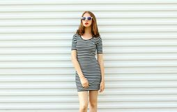 Stylish young woman in striped dress posing on white wall. Background stock images