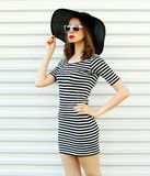 Stylish young woman in striped dress, summer straw hat posing on white wall. Background royalty free stock photography