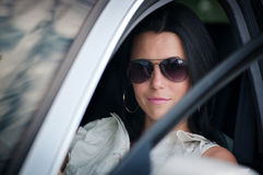Stylish young woman in sunglasses driving a car Royalty Free Stock Image
