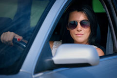 Stylish young woman in sunglasses driving a car royalty free stock photos
