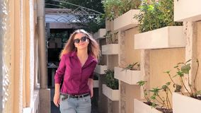 Stylish young woman in sunglasses looks into the camera stock video