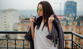 Stylish young woman in sunglasses posing in leather jacket on urban background. Close up stock images