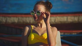 Stylish and young woman in sunglasses sunbathing in the sunshine summertime stock footage