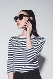 Stylish young woman in sunglasses talking on smartphone isolated on grey Stock Images