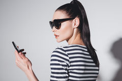 Stylish young woman in sunglasses using smartphone isolated on grey Royalty Free Stock Photo