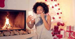 Stylish young woman taking a Christmas selfie stock video footage