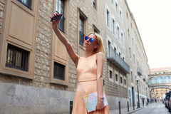 Stylish young woman taking self portrait with smart phone Stock Images