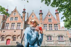 Stylish young female tourist takes a selfie on a mobile phone in Bruges, Belgium. royalty free stock photography