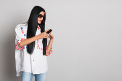 Stylish young woman uses a cell phone Royalty Free Stock Photos