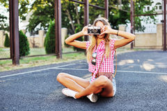 Stylish young woman using a camera to take photo outdoors Stock Images