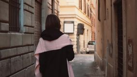 Stylish young woman walking alone through the alley. Girl going in the side street, exploring the city. Pretty young woman walking alone through the alley. Girl stock video