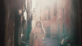 Stylish young woman walking alone through the alley at morning. Girl going in side street, enjoying the time outside. Pretty young woman walking alone through stock video footage