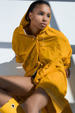 Stylish young woman wearing yellow raincoat looking away. Pensive stylish young woman wearing yellow raincoat looking away Stock Photography