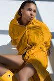Stylish young woman wearing yellow raincoat looking away Stock Photography