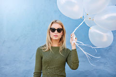 Stylish young woman with white balloons. Portrait of stylish young woman with white balloons against blue wall. Trendy female model holding balloons Royalty Free Stock Photo