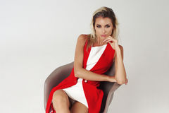 Stylish young woman in white dress and red jacket Stock Photo