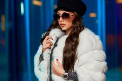 Stylish young woman in white fur coat and round sunglasses stock photo