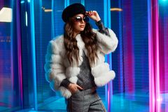 Stylish young woman in white fur coat and round sunglasses stock image