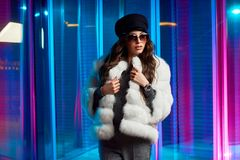 Stylish young woman in white fur coat and round sunglasses stock images