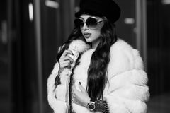 Stylish young woman in white fur coat and round sunglasses royalty free stock photos