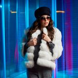 Stylish young woman in white fur coat and round sunglasses royalty free stock image