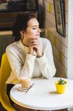 Beautiful brunette woman in white sweater in a cafe drinking coffee. Hipster white and yellow interior of cafe stock image