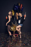 Stylish young women posing with bottles of alcohol beverages and shiny balloons Royalty Free Stock Images
