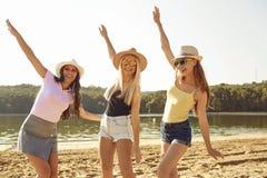 Playful young women dancing on beach royalty free stock photos