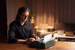 A stylish young writer working on vintage typewriter, write a new book. Man in black shirt and eye glass in apartment. stock photos