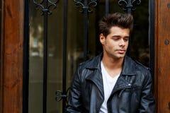 Stylishly-ντυμένος νεαρός άνδρας που στέκεται στην οδό ενάντια στην ξύλινη πόρτα στοκ φωτογραφία με δικαίωμα ελεύθερης χρήσης