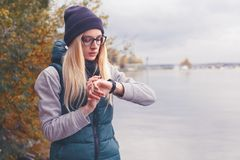 Stylishly dressed blonde sportswoman adjusts an electronic bracelet-pedometer standing on the lake shore. Autumn sports. Style. Travel and healthy lifestyle Royalty Free Stock Photo