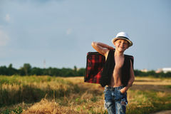 Stylishly dressed boy in field with suitcase Stock Photo