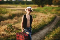 Stylishly dressed boy in field with suitcase Royalty Free Stock Image