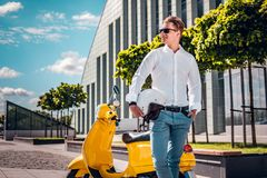 Handsome man holding a helmet and looking sideways standing next to a scooter at the street. Stylishly dressed man holding a helmet and looking sideways standing royalty free stock photo