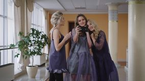Stylishly dressed models made selfie on smartphone when one of them remind they need to rush to the fashion show. Silly. Funny girls running away in the stock video