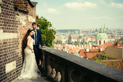 Stylishly dressed newlywed couple is standing on the old meadieval balcony and enjoying the panorama of Prague. Stylishly dressed newlywed couple is standing on Royalty Free Stock Photos