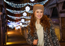 Stylishly dressed woman standing in front of Christmas lights Stock Images
