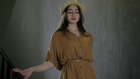Stylishly dressed young beautiful girl in elegant hat go down stairs handbag in hand, concept lifestyle fashion and beauty. Stylishly dressed young beautiful stock video
