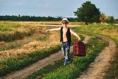 Stylishly klädd pojke i fält med resväskan Arkivbild