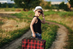 Stylishly klädd pojke i fält med resväskan Royaltyfria Foton