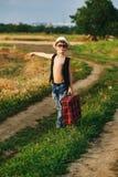 Stylishly klädd pojke i fält med resväskan Fotografering för Bildbyråer