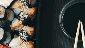 Stylishly laid sushi set on a black wooden background next to soy sauce and Chinese bamboo sticks. Various sushi rolls. A stylishly laid sushi set on a black stock video footage