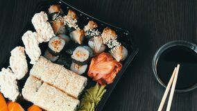 Stylishly laid sushi set on a black wooden background next to soy sauce and Chinese bamboo sticks. Various sushi rolls. A stylishly laid sushi set on a black stock video