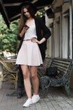 Stylishly ubierająca dziewczyna stoi blisko, podrzuca newsfeed w facebook i marmurowego stolik do kawy i drewnianego banch jest w obrazy royalty free