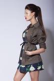 stylishness Moderne Frau, die im eleganten Mantel aufwirft lizenzfreie stockfotos