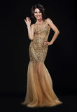 Stylishness. Well-dressed Young Woman in Long Golden Dress Royalty Free Stock Photo
