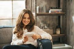 Stylisht kobieta bawić się z smartphone obsiadaniem w loft pokoju Obrazy Royalty Free