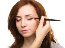 Stylist is applying eyeshadow for young girl Royalty Free Stock Image