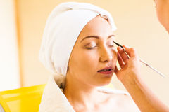 Stylist applying make-up to young beautiful woman Royalty Free Stock Photo